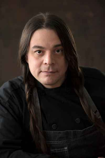 Portrait of Chef Sean Sherman wearing a black long-sleeved shirt against a black background. He has long, black hair loosely braided.