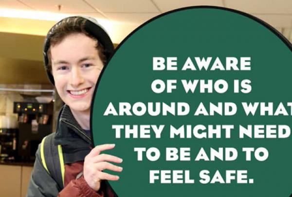 "A student holding a sign reading ""Be aware of who is around and what they might need to be and to feel safe"""